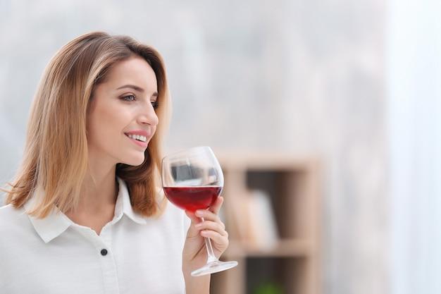 Bella giovane donna con un bicchiere di vino che si rilassa a casa