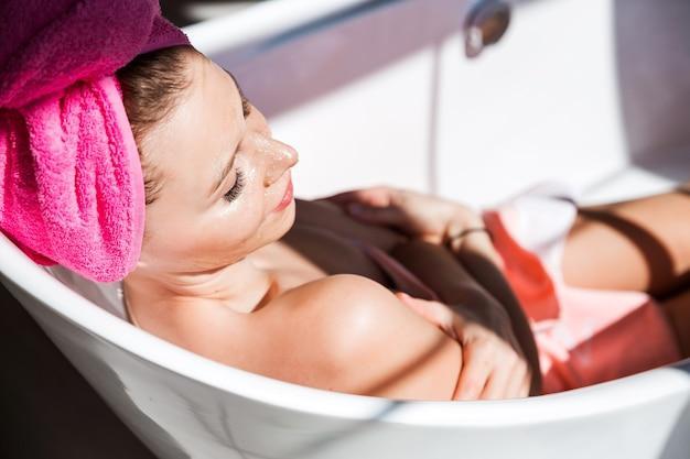 Una bellissima giovane donna con una maschera d'oro sul viso posa in una vasca da bagno in ceramica bianca