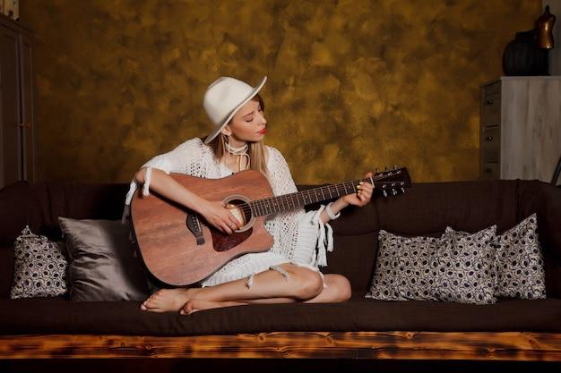 Bella giovane donna con la chitarra all'interno della stanza. donna carina sul divano con la chitarra in mano. concetto di apprendimento a casa o di suonare la chitarra a casa. spazio di copyright per sito o banner o logo