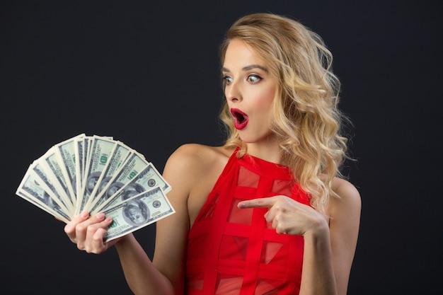 Bella giovane donna con acconciatura e trucco in un vestito rosso che tiene i dollari