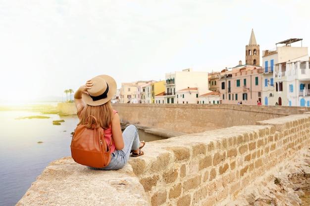 Bella giovane donna con cappello seduto sul muro guardando la storica città di alghero in sardegna, italy