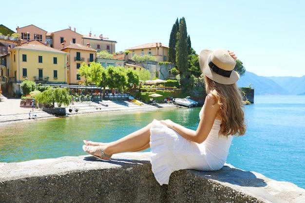Bella giovane donna con il cappello che si siede sul muro guardando la città di varenna sul lago di como, italia