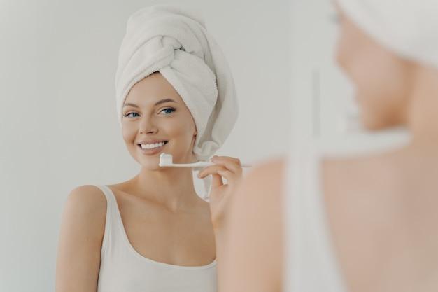 Bella giovane donna con un sano sorriso perfetto lavarsi i denti e guardarsi allo specchio, attraente giovane donna che indossa un asciugamano da bagno bianco sulla testa in piedi nel bagno di casa. concetto di igiene orale