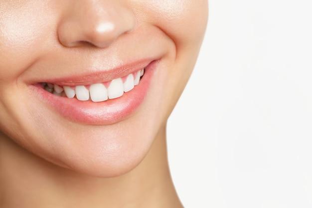 Bella giovane donna con denti sani su sfondo bianco.