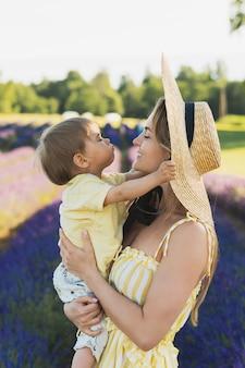 Bella e giovane donna con il suo piccolo figlio carino in un campo di lavanda