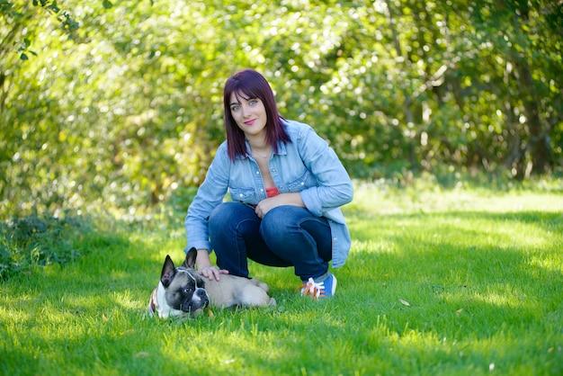 Bella giovane donna con il suo cane bulldog francese