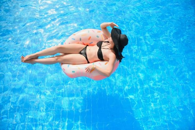 Bella giovane donna con ciambella gonfiabile in piscina blu
