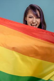 Bella giovane donna con bandiera lgbt. lesbiche con capelli tinti di viola e piercing con la bandiera della comunità gay e lesbica