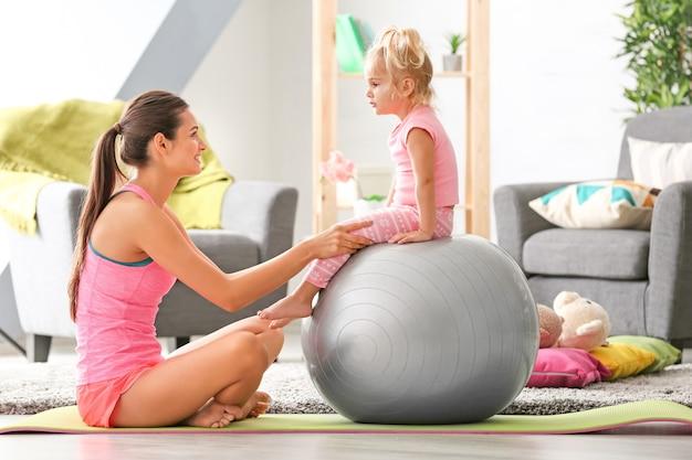 Bella giovane donna con la piccola figlia che si allena a casa