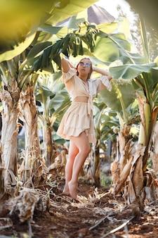 Una bella giovane donna con lunghi capelli biondi di aspetto europeo si trova vicino ai banani. ragazza nella foresta tropicale in una giornata di sole estivo. messa a fuoco selettiva