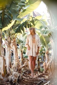 Una bella giovane donna con lunghi capelli biondi di aspetto europeo si trova vicino ai banani. ragazza nella foresta tropicale in una soleggiata giornata estiva
