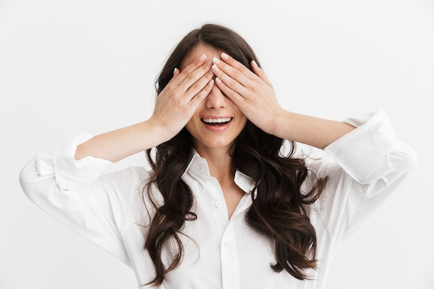 Bella giovane donna con lunghi capelli castani ricci che indossa una camicia bianca in piedi isolata sul muro bianco, copre la faccia