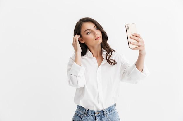 Bella giovane donna con lunghi capelli castani ricci che indossa una camicia bianca in piedi isolata sul muro bianco, facendo un selfie