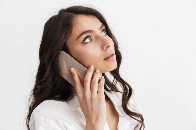 Bella giovane donna con lunghi capelli castani ricci che indossa una camicia bianca in piedi isolata sul muro bianco, parlando al telefono cellulare, guardando in alto