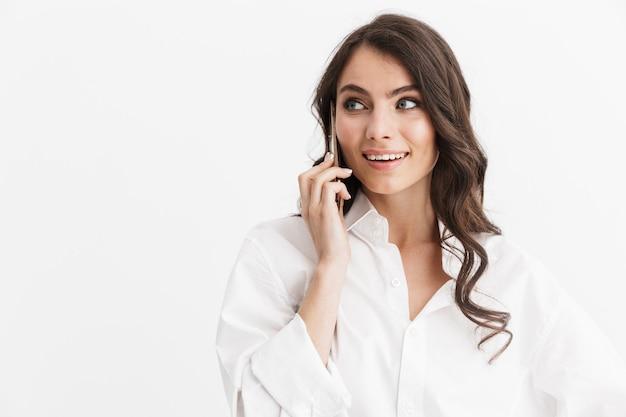 Bella giovane donna con lunghi capelli castani ricci che indossa una camicia bianca in piedi isolata sul muro bianco, parlando al cellulare