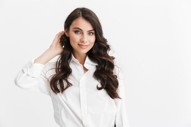 Bella giovane donna con lunghi capelli castani ricci che indossa una camicia bianca in piedi isolato su un muro bianco