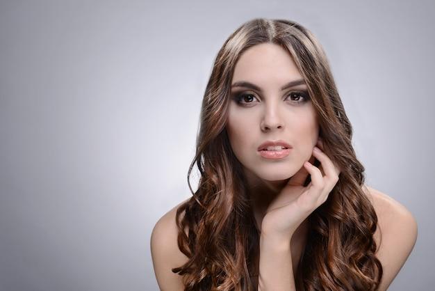 Bella giovane donna con i capelli lunghi su sfondo grigio