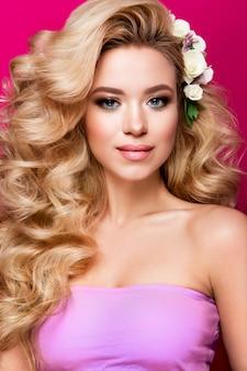 Bella giovane donna con capelli lunghi che posano sulla parete brillante rosa. pelle sana e capelli lunghi e lisci. labbra rosa