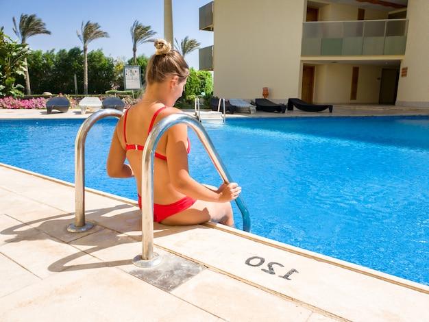 Bella giovane donna con capelli lunghi che si siede a bordo piscina nella lussuosa villa. donna che si rilassa e si diverte durante le vacanze estive.