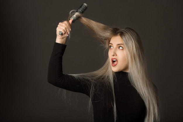 Bella giovane donna con i capelli lunghi su uno sfondo bianco si pettina i capelli