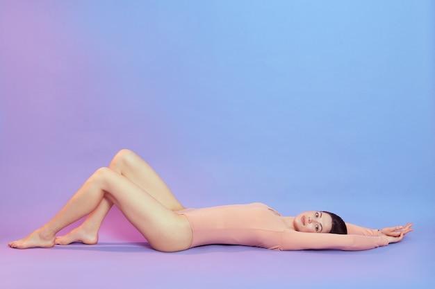 Bella giovane donna con le gambe lunghe che indossa un body beige sdraiato sul pavimento e alzando lo sguardo, femmina con il corpo perfetto alzando le gambe, in posa isolata sopra la parete blu con luce al neon rosa