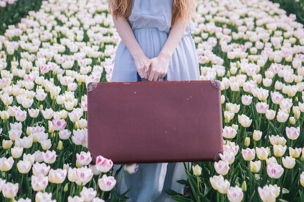 Bella giovane donna con lunghi capelli rossi che indossa in abito bianco in piedi con la vecchia valigia vintage sul campo di tulipani colorati.