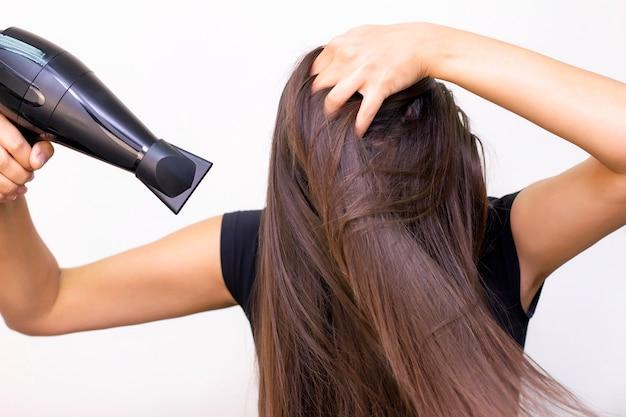 Bella giovane donna con capelli castani lunghi e lisci si prende cura dei suoi capelli