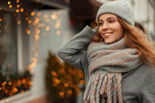 Bella giovane donna con un magnifico sorriso in un cappotto grigio alla moda e un cappello invernale lavorato a maglia con una sciarpa vintage che cammina all'aperto durante le vacanze