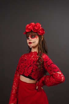 Bella giovane donna con trucco e abbigliamento dia de los muertos su sfondo nero.