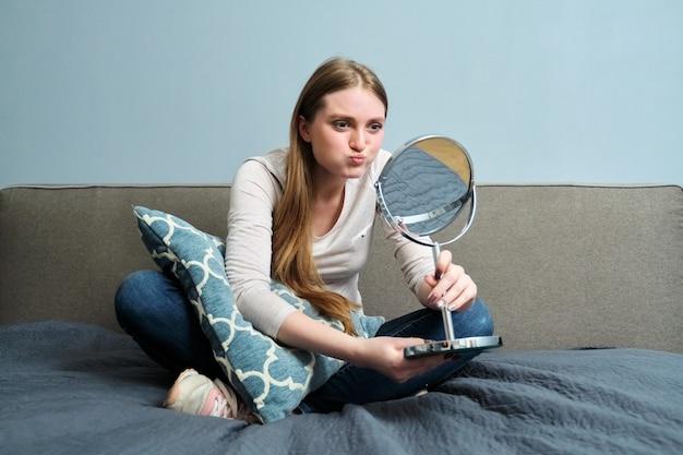 Bella giovane donna con specchio per il trucco seduto a casa a letto, la ragazza fa emozioni, si guarda allo specchio