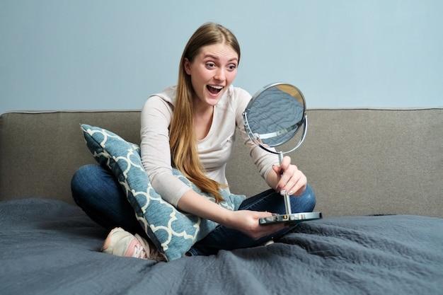 Bella giovane donna con specchio per il trucco seduta a casa a letto, la ragazza fa emozioni, si guarda allo specchio