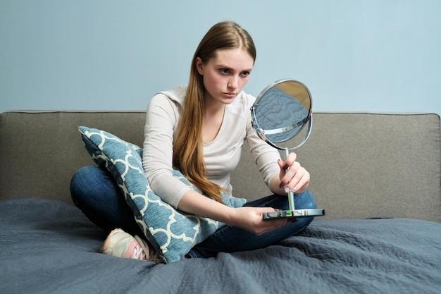 Bella giovane donna con specchio per il trucco seduto a casa a letto