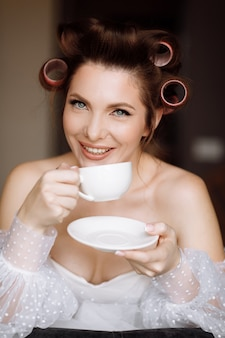 Bella giovane donna con il trucco, bigodini vestito in abito bianco e rilassante a casa con una tazza di caffè o tè