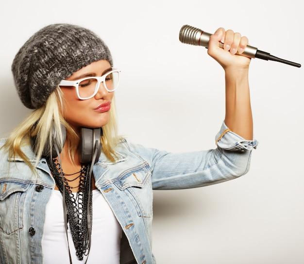Bella giovane donna con microfono e cuffie su sfondo grigio
