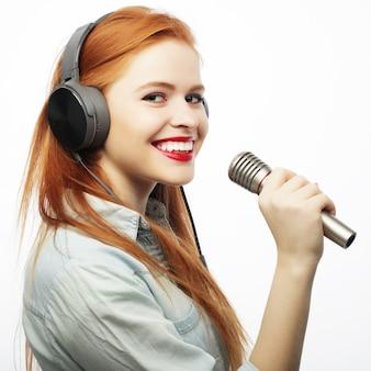 Bella giovane donna con microfono e cuffie su grigio
