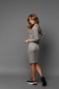 Bella giovane donna con un corpo perfetto in una gonna stretta e scarpe da ginnastica in posa con la schiena sullo sfondo grigio, isolato