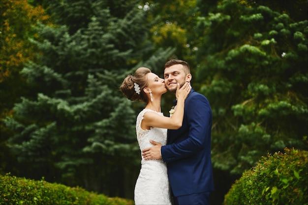 Bella giovane donna con un corpo perfetto e acconciatura da sposa in abiti di pizzo abbracci e baci