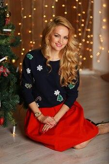 Bella giovane donna con un trucco perfetto e capelli alla moda seduta sul pavimento vicino all'albero di natale in interni decorati per natale