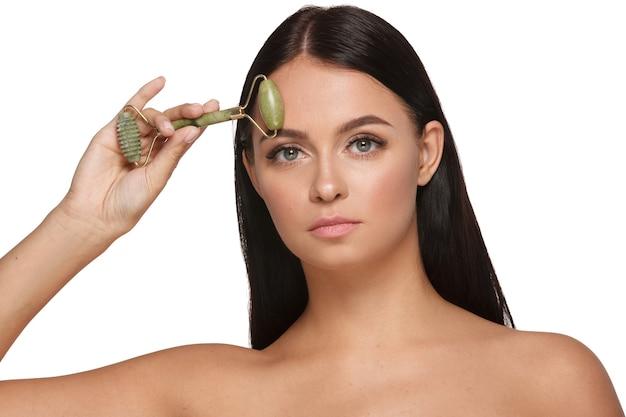 Bella giovane donna con una pelle perfetta che indossa un asciugamano sulla testa utilizzando un rullo frontale di giada con pietre di quarzo naturale su bianco