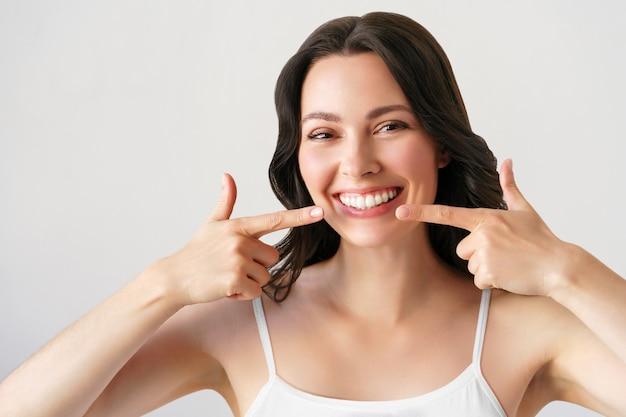 Bella giovane donna con un sorriso perfetto. isolato su bianco. donna dopo la procedura di sbiancamento dei denti