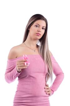 Bella giovane donna con il vestito rosa che tiene un nastro rosa di consapevolezza per il cancro al seno.
