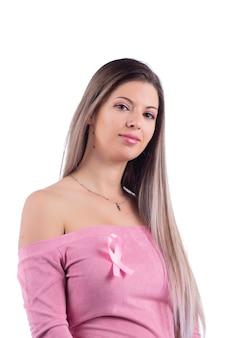 Bella giovane donna con un vestito rosa con un nastro rosa di consapevolezza per il cancro al seno.