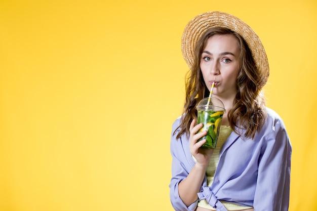 Bella giovane donna con bicchiere di plastica di cocktail fresco fresh