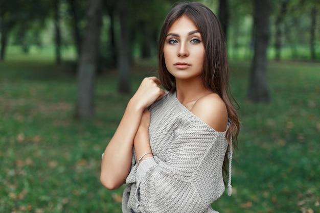 Bella giovane donna con un bel viso in un maglione grigio nel parco