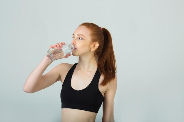 Bella giovane donna con i capelli rossi in abbigliamento sportivo con una bottiglia d'acqua