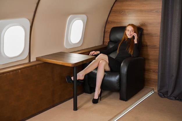 Bella giovane donna con i capelli rossi, parlando al telefono nella cabina di un jet privato