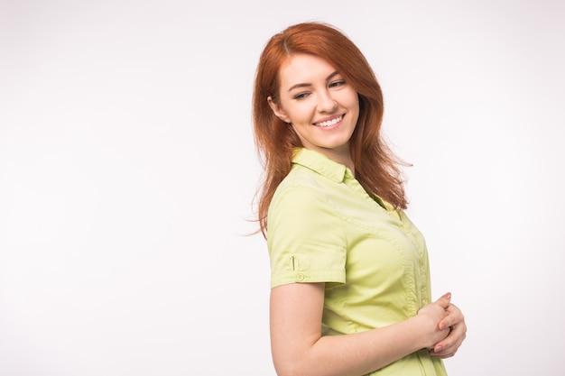 Bella giovane donna con i capelli rossi con lo spazio della copia