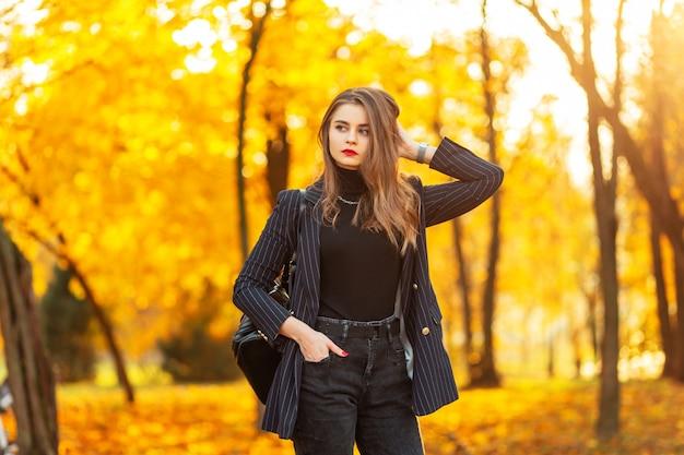 La bella giovane donna con le labbra rosse in un vestito elegante di modo con un blazer, un maglione e uno zaino cammina nel parco con fogliame giallo-arancio variopinto al tramonto