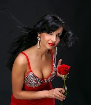 Bella giovane donna con rosa rossa su sfondo scuro