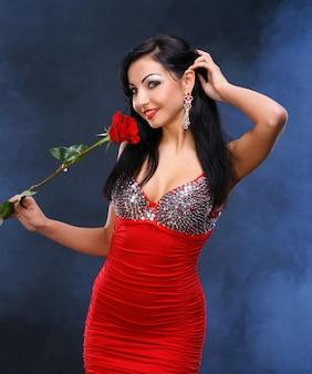 Bella giovane donna con una rosa rossa su uno sfondo fumoso
